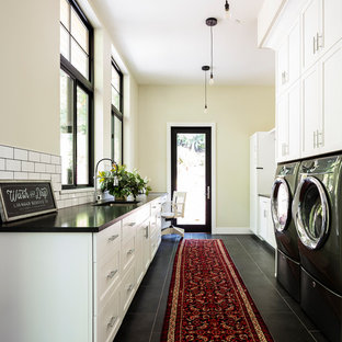 Design ideas for a large rural galley separated utility room in Seattle with a submerged sink, shaker cabinets, white cabinets, granite worktops, yellow walls, porcelain flooring, a side by side washer and dryer, black floors and black worktops.