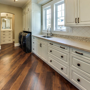 Dedicated laundry room - mid-sized traditional l-shaped medium tone wood floor and brown floor dedicated laundry room idea in Other with an undermount sink, raised-panel cabinets, distressed cabinets, beige walls and a side-by-side washer/dryer