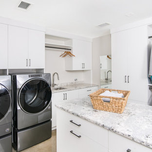 Mid-sized minimalist u-shaped concrete floor laundry closet photo in Detroit with an undermount sink, flat-panel cabinets, white cabinets, quartzite countertops, white walls and a side-by-side washer/dryer