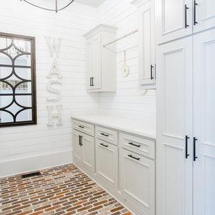 Idee per una grande lavanderia multiuso chic con lavello stile country, ante con bugna sagomata, ante grigie, top in quarzo composito, pareti bianche, pavimento in mattoni, lavatrice e asciugatrice affiancate, pavimento rosso e top bianco