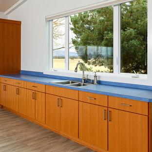 Idéer för att renovera ett mellanstort lantligt blå linjärt blått grovkök, med en dubbel diskho, släta luckor, skåp i mellenmörkt trä, träbänkskiva, beige väggar, mörkt trägolv och brunt golv