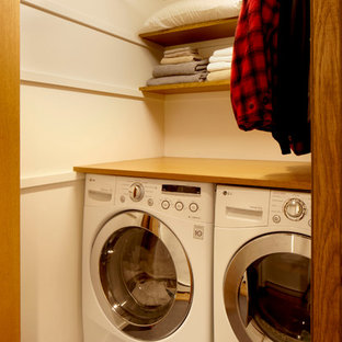 This is an example of a midcentury laundry cupboard in Seattle with a side-by-side washer and dryer.
