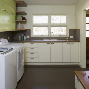 Midcentury laundry room in DC Metro with green cabinets and brown floor.