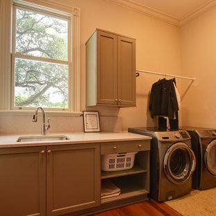 Ispirazione per una lavanderia tradizionale di medie dimensioni con pavimento marrone, lavello sottopiano, ante in stile shaker, ante grigie, pareti beige, pavimento in legno massello medio e lavatrice e asciugatrice affiancate