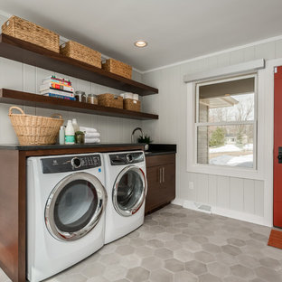 Design ideas for a mid-sized midcentury single-wall laundry room in Milwaukee with an undermount sink, dark wood cabinets, granite benchtops, grey walls, ceramic floors, a side-by-side washer and dryer, grey floor, black benchtop and open cabinets.
