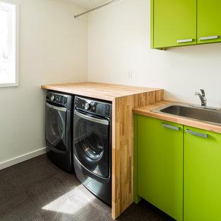 Свежая идея для дизайна: маленькая прямая прачечная в стиле ретро с накладной раковиной, плоскими фасадами, зелеными фасадами, деревянной столешницей, белыми стенами и со стиральной и сушильной машиной рядом - отличное фото интерьера