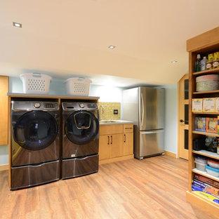 Ispirazione per una piccola lavanderia multiuso minimalista con pareti beige, pavimento in legno massello medio, pavimento beige, lavello da incasso, ante lisce, ante in legno chiaro, top in quarzite, lavatrice e asciugatrice affiancate e top grigio