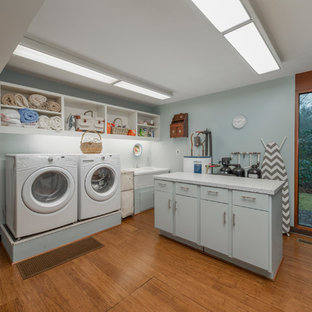 Cette image montre une grand buanderie vintage dédiée avec un mur bleu, des machines côte à côte, un évier 2 bacs, un placard sans porte, des portes de placard blanches, un plan de travail gris et un sol en liège.