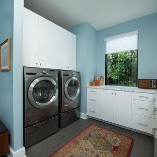 Immagine di una piccola sala lavanderia moderna con ante lisce, ante bianche, top in laminato, pareti blu, pavimento in gres porcellanato, lavatrice e asciugatrice affiancate, pavimento grigio e top bianco