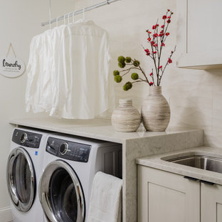 Laundry room - contemporary single-wall gray floor laundry room idea in Boston with an undermount sink, shaker cabinets, gray cabinets, a side-by-side washer/dryer and gray countertops