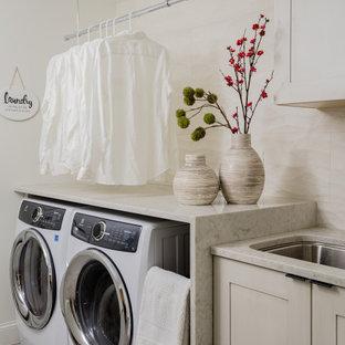 Inredning av en modern grå linjär grått tvättstuga, med en undermonterad diskho, skåp i shakerstil, grå skåp, en tvättmaskin och torktumlare bredvid varandra och grått golv