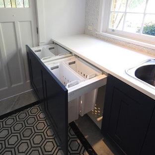 シドニーの中くらいのモダンスタイルのおしゃれな洗濯室 (I型、ドロップインシンク、落し込みパネル扉のキャビネット、黒いキャビネット、クオーツストーンカウンター、白い壁、大理石の床、上下配置の洗濯機・乾燥機、グレーの床、白いキッチンカウンター) の写真