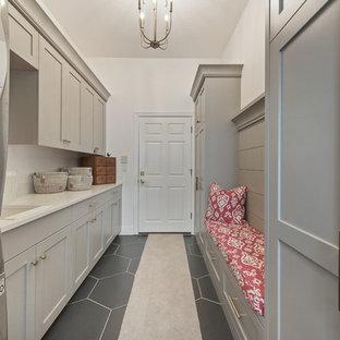 Idéer för mellanstora lantliga linjära beige grovkök, med skåp i shakerstil, grå skåp, bänkskiva i kvartsit, klinkergolv i keramik, en tvättpelare, svart golv, en undermonterad diskho och vita väggar