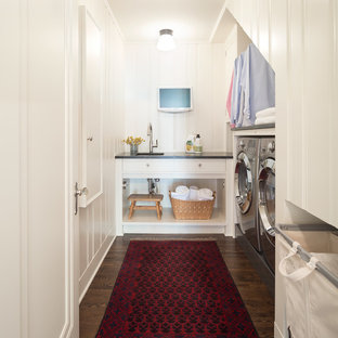 Example of a classic u-shaped dark wood floor and brown floor dedicated laundry room design in Minneapolis with an undermount sink, white cabinets, white walls and black countertops