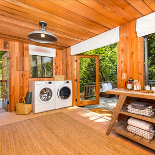 Example of a large mountain style light wood floor and orange floor utility room design in San Francisco with a side-by-side washer/dryer, open cabinets and medium tone wood cabinets