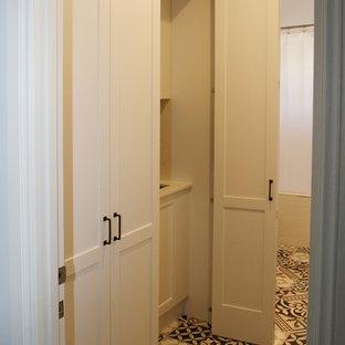 Inspiration pour une buanderie linéaire style shabby chic multi-usage et de taille moyenne avec un placard à porte shaker, des portes de placard blanches, un plan de travail en surface solide, un mur blanc, un sol en carrelage de céramique, un évier encastré, le lave-linge et le sèche-linge forment un seul appareil électroménager, un sol multicolore et un plan de travail blanc.
