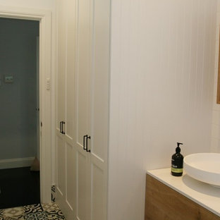 Mid-sized traditional single-wall utility room in Sydney with an undermount sink, shaker cabinets, white cabinets, solid surface benchtops, white walls, ceramic floors, an integrated washer and dryer, multi-coloured floor and white benchtop.