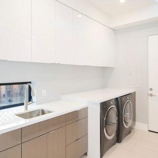 Idéer för stora funkis linjära vitt tvättstugor enbart för tvätt, med en undermonterad diskho, släta luckor, vita skåp, bänkskiva i kvarts, vita väggar, klinkergolv i porslin, en tvättmaskin och torktumlare bredvid varandra och beiget golv