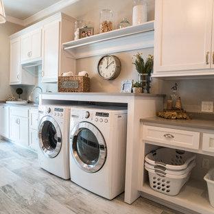 Inspiration för en lantlig grå linjär grått tvättstuga enbart för tvätt, med en undermonterad diskho, luckor med infälld panel, vita skåp och en tvättmaskin och torktumlare bredvid varandra