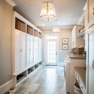 Idee per una grande lavanderia country con ante bianche, top in quarzo composito, pareti grigie, pavimento in gres porcellanato, lavatrice e asciugatrice affiancate e ante con riquadro incassato
