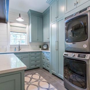 Exemple d'une buanderie nature avec un placard à porte shaker, des portes de placard turquoises, un mur blanc, un sol en carrelage de céramique, des machines superposées, un sol gris et un plan de travail blanc.