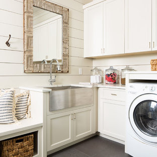 Inspiration for a mid-sized farmhouse l-shaped gray floor and concrete floor utility room remodel in Atlanta with a farmhouse sink, recessed-panel cabinets, white cabinets, white walls, white countertops and quartz countertops