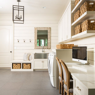 Example of a mid-sized country l-shaped concrete floor and gray floor utility room design in Atlanta with a farmhouse sink, recessed-panel cabinets, white cabinets, quartz countertops, white walls, a side-by-side washer/dryer and white countertops