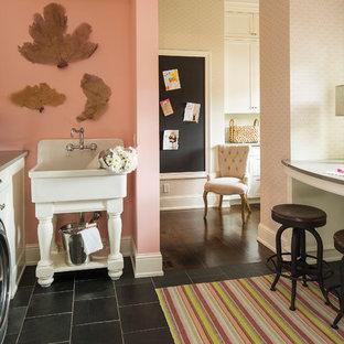 Idée de décoration pour une buanderie tradition avec des portes de placard blanches, un sol noir, un évier utilitaire, un placard à porte shaker, un mur rose et des machines côte à côte.