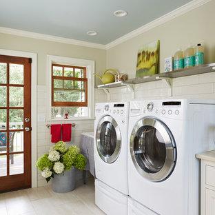 Lantlig inredning av en mellanstor linjär tvättstuga, med en allbänk, luckor med infälld panel, vita skåp, bänkskiva i kvarts och klinkergolv i porslin