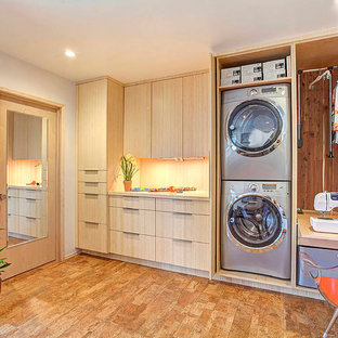 Inspiration for a contemporary single-wall utility room in Orange County with flat-panel cabinets, light wood cabinets, grey walls, a concealed washer and dryer and cork flooring.