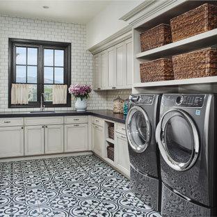Ispirazione per una sala lavanderia mediterranea con lavello sottopiano, ante con riquadro incassato, ante grigie, paraspruzzi bianco, paraspruzzi con piastrelle diamantate, pareti bianche, lavatrice e asciugatrice affiancate, pavimento multicolore e top nero