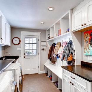 Inredning av ett klassiskt brun parallellt brunt grovkök, med luckor med infälld panel, vita skåp, grå väggar, en tvättmaskin och torktumlare bredvid varandra och brunt golv