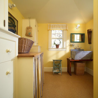 Large country single-wall dedicated laundry room in Portland Maine with an utility sink, open cabinets, dark wood cabinets, wood benchtops, yellow walls, laminate floors, a side-by-side washer and dryer, beige floor and brown benchtop.
