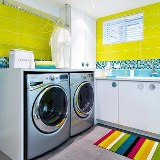 Inspiration pour une buanderie design dédiée avec un placard à porte plane, des portes de placard blanches, un mur jaune, des machines côte à côte et un sol gris.