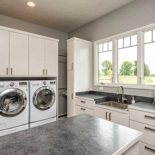 Bild på en stor funkis grå grått tvättstuga enbart för tvätt, med en tvättmaskin och torktumlare bredvid varandra, en enkel diskho, släta luckor, vita skåp och grå väggar