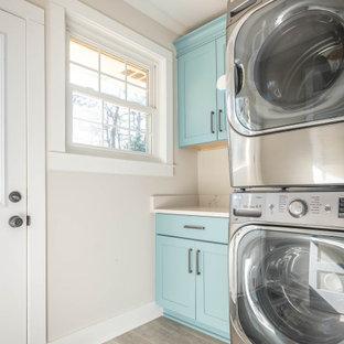 Esempio di una piccola lavanderia moderna con ante con riquadro incassato, ante blu, paraspruzzi beige, pareti beige, parquet chiaro, lavatrice e asciugatrice a colonna, pavimento beige e top bianco