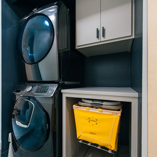 Exempel på en liten maritim grå linjär grått liten tvättstuga, med öppna hyllor, grå skåp, träbänkskiva, svarta väggar, klinkergolv i porslin, en tvättpelare och grått golv