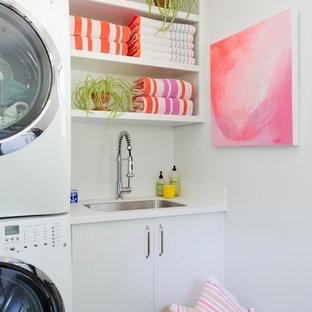 Exempel på en mellanstor modern u-formad tvättstuga enbart för tvätt, med släta luckor, vita skåp, vita väggar, en tvättpelare, en undermonterad diskho, mörkt trägolv och brunt golv