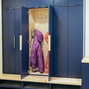 Пример оригинального дизайна: большая п-образная универсальная комната в стиле модернизм с фасадами в стиле шейкер, синими фасадами, синим фартуком, фартуком из стеклянной плитки, полом из керамогранита, серым полом, одинарной раковиной, деревянной столешницей, желтыми стенами, со стиральной и сушильной машиной рядом и коричневой столешницей