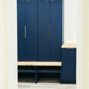 Idéer för att renovera ett stort funkis brun u-format brunt grovkök, med skåp i shakerstil, blått stänkskydd, stänkskydd i glaskakel, klinkergolv i porslin, grått golv, blå skåp, en enkel diskho, träbänkskiva, gula väggar och en tvättmaskin och torktumlare bredvid varandra