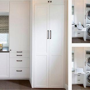 Immagine di una lavanderia multiuso classica con ante con riquadro incassato, ante bianche, pareti bianche, lavatrice e asciugatrice a colonna, pavimento marrone, top grigio, top in cemento e parquet scuro