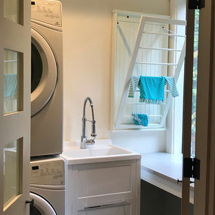 This is an example of a small arts and crafts u-shaped utility room in Seattle with an utility sink, shaker cabinets, white cabinets, quartz benchtops, white walls, slate floors, a stacked washer and dryer, green floor and grey benchtop.