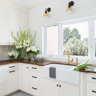 Inspiration for a modern terra-cotta tile and blue floor laundry room remodel in Albuquerque with a farmhouse sink, recessed-panel cabinets, white cabinets, wood countertops, white walls and brown countertops