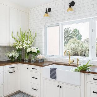 Cette photo montre une buanderie moderne avec un évier de ferme, un placard avec porte à panneau encastré, des portes de placard blanches, un plan de travail en bois, un mur blanc, un sol en carreau de terre cuite, un sol bleu et un plan de travail marron.