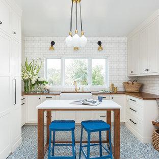Cette image montre une buanderie traditionnelle en U avec un évier de ferme, des portes de placard blanches, un plan de travail en bois, un mur blanc, un sol en carreau de terre cuite, des machines dissimulées, un sol bleu et un placard à porte shaker.