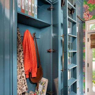 Inredning av ett klassiskt mellanstort vit parallellt vitt grovkök, med en undermonterad diskho, blå skåp, bänkskiva i kvarts, blått stänkskydd, stänkskydd i tunnelbanekakel, blå väggar, mörkt trägolv och en tvättmaskin och torktumlare bredvid varandra