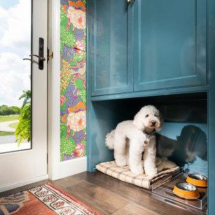 Klassisk inredning av ett mellanstort vit parallellt vitt grovkök, med en undermonterad diskho, blå skåp, bänkskiva i kvarts, blått stänkskydd, stänkskydd i tunnelbanekakel, blå väggar, mörkt trägolv och en tvättmaskin och torktumlare bredvid varandra