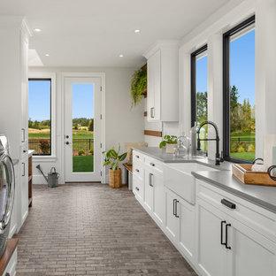 Lantlig inredning av ett mycket stort grå l-format grått grovkök, med en rustik diskho, skåp i shakerstil, vita skåp, bänkskiva i kvarts, vita väggar, klinkergolv i keramik, en tvättmaskin och torktumlare bredvid varandra och grått golv