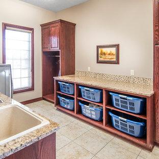 Immagine di una sala lavanderia tradizionale di medie dimensioni con lavello a vasca singola, ante con bugna sagomata, ante in legno bruno, top in granito, pareti beige, pavimento con piastrelle in ceramica e lavatrice e asciugatrice affiancate