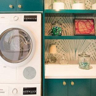 Modern inredning av en liten tvättstuga, med släta luckor, flerfärgade väggar, en tvättpelare och blå skåp